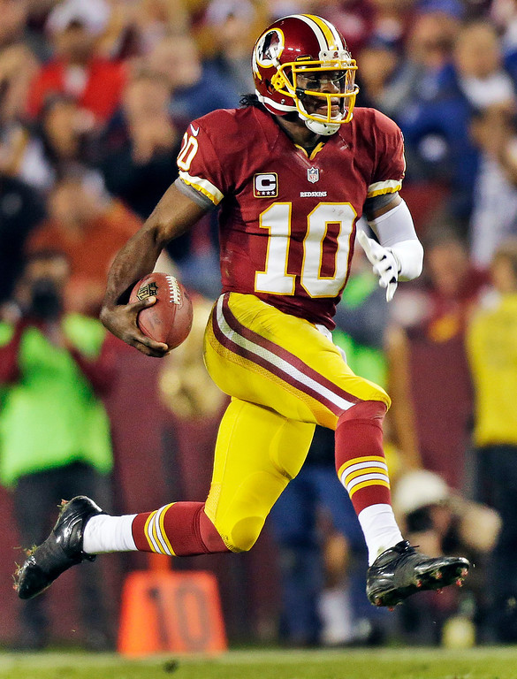 . Washington Redskins quarterback Robert Griffin III scrambles with the ball during the second half of an NFL football game against the New York Giants in Landover, Md., Monday, Dec. 3, 2012. (AP Photo/Evan Vucci)