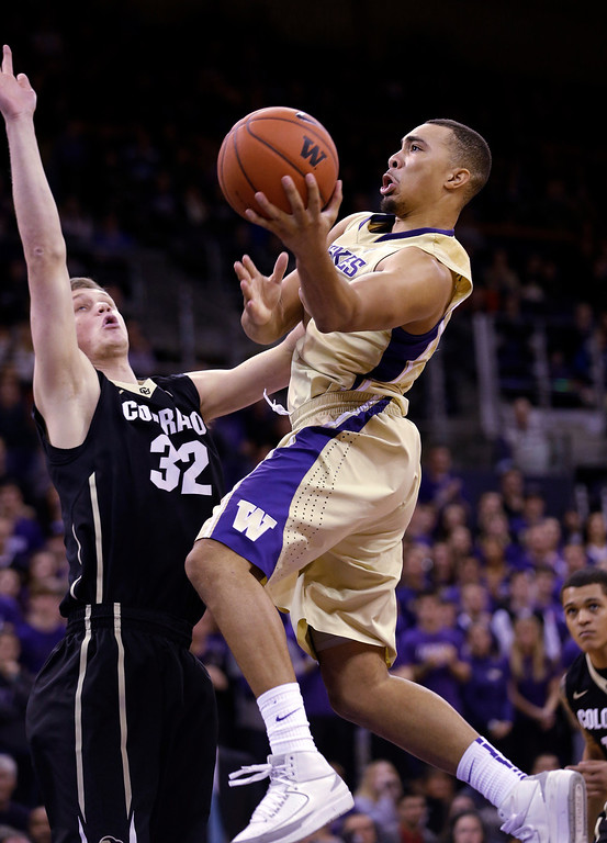 . Washington\'s Andrew Andrews, right, shoots past Colorado\'s Ben Mills in the second half of an NCAA men\'s basketball game Sunday, Jan. 12, 2014, in Seattle. Washington won 71-54. (AP Photo/Elaine Thompson)
