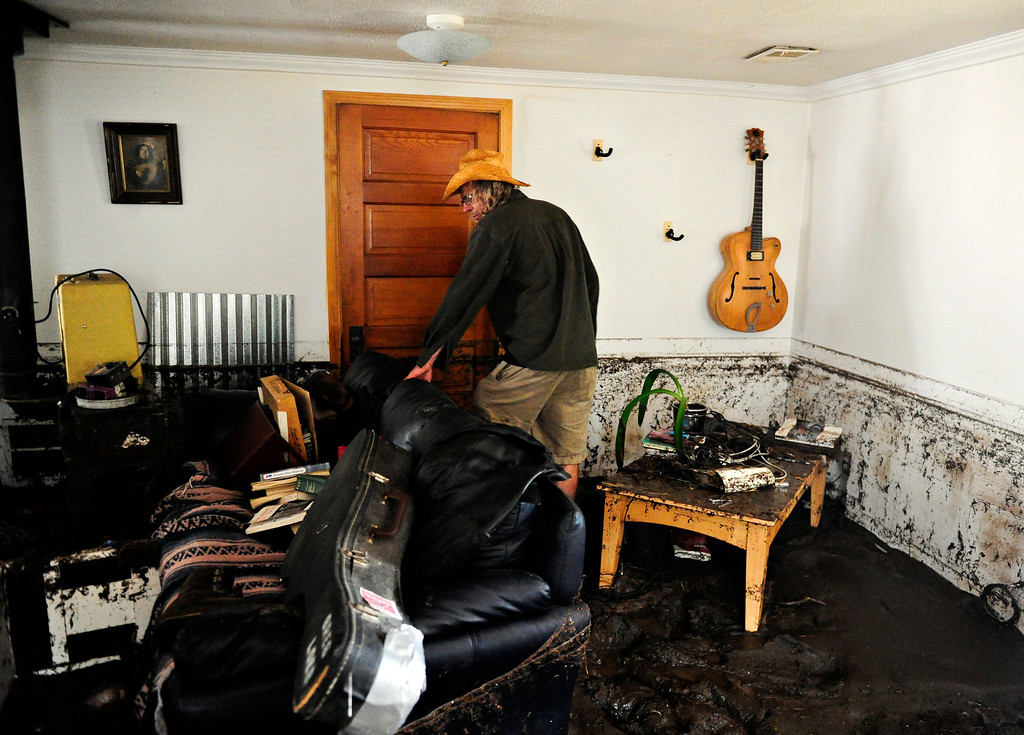 ". Gary McCrumb wades through about six inches of mud in his home, 414 Park Dr., in Lyons Friday, Sept. 13, 2013, as he collects valuables. McCrumb is planning to stay with friends in town. ""We\'re all taking care of each other,\"" said McCrumb. (Greg Lindstrom/Times-Call)"