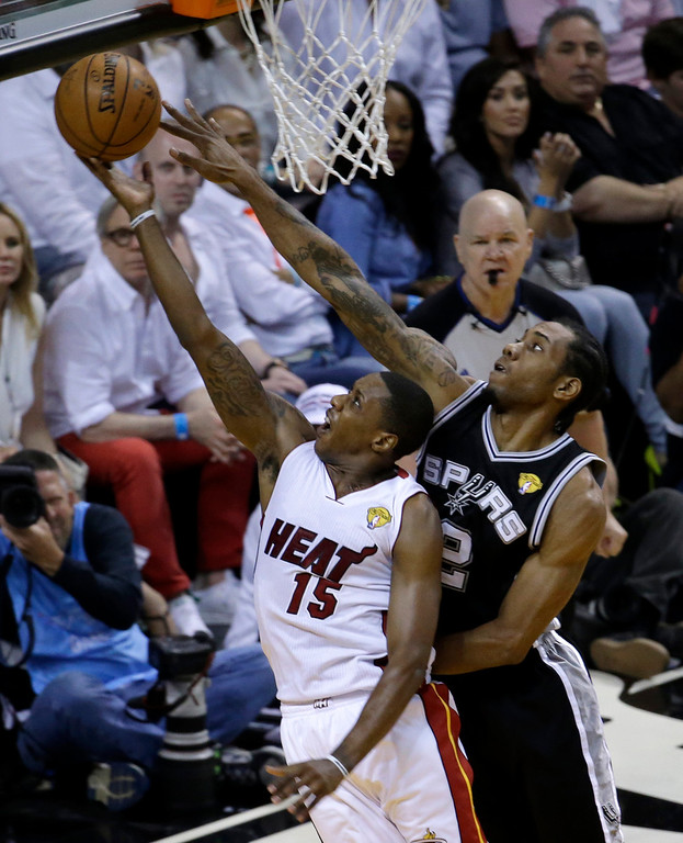 . Miami Heat guard Mario Chalmers (15) goes to the basket as San Antonio Spurs forward Kawhi Leonard (2) defends in the first half in Game 4 of the NBA basketball finals, Thursday, June 12, 2014, in Miami. (AP Photo/Wilfredo Lee)