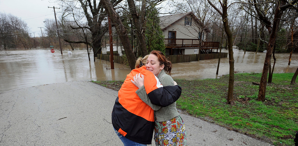 . Jennifer Waters, left, hugs Chrissy Wild, as the flooded Hickory Creek  passes near the home Wild was going to buy in New Lenox, Ill. on Thursday April 18,  2013. It was going to be her first home. a. (AP Photo/SouthtownStar, Matt Marton)