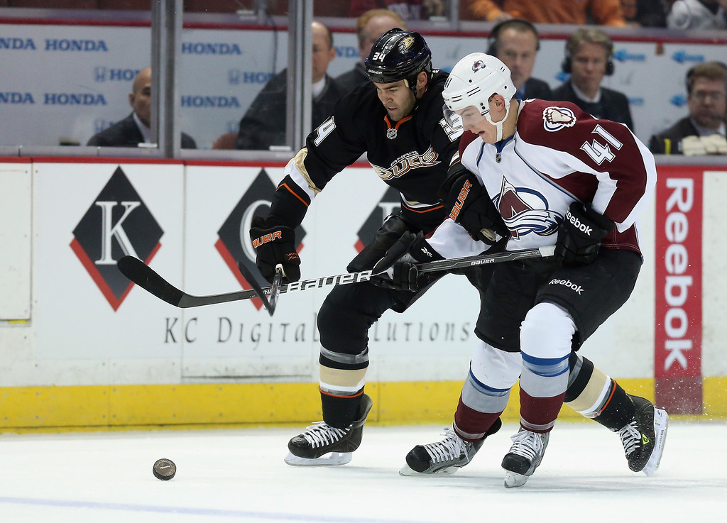 . Daniel Winnik #34 of the Anaheim Ducks and Tyson Barrie #41 of the Colorado Avalanche fight for the puck in the first period at Honda Center on February 24, 2013 in Anaheim, California.  (Photo by Jeff Gross/Getty Images)