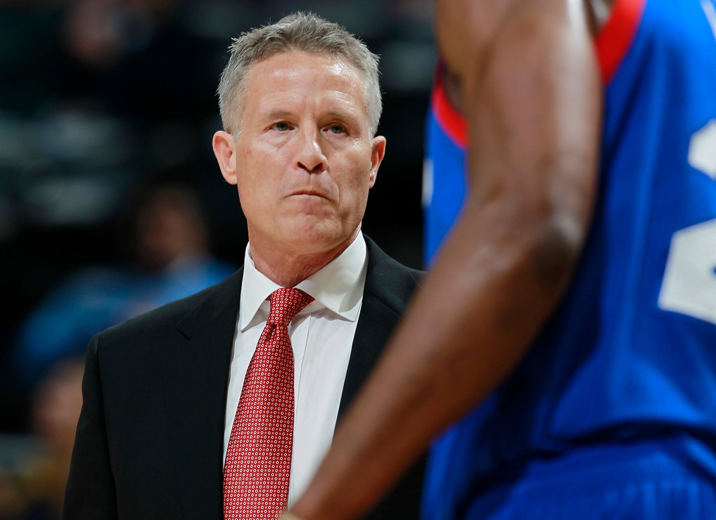 . Philadelphia 76ers coach Brett Brown, back, confers with forward Thaddeus Young during a timeout against the Denver Nuggets in the first quarter of an NBA basketball game in Denver on Wednesday, Jan. 1, 2014. (AP Photo/David Zalubowski)