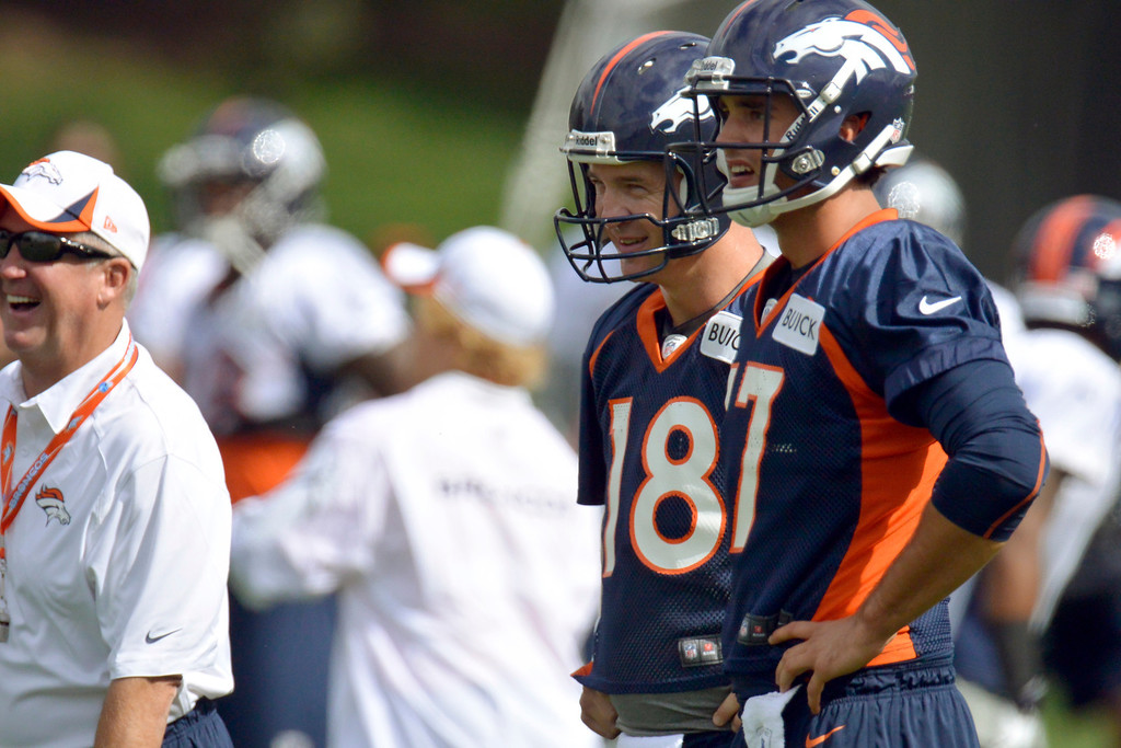 . Denver Broncos quarterbacks Peyton Manning (18) and Brock Osweiler (17) look on as head coach John Fox laughs during opening day of training camp July 25, 2013 at Dove Valley. (Photo By John Leyba/The Denver Post)