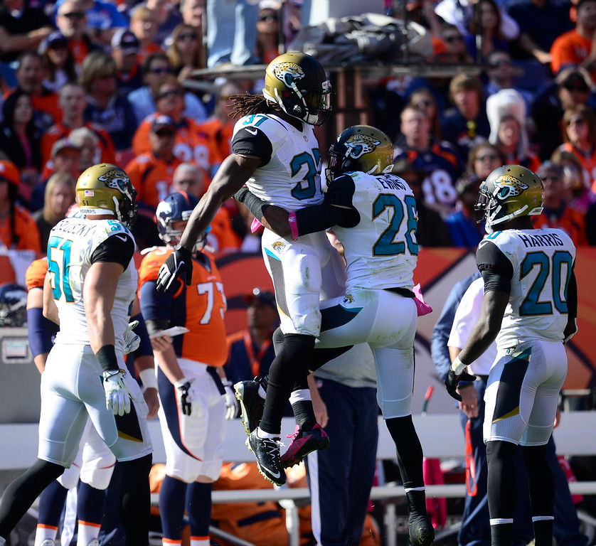 . Jacksonville Jaguars strong safety John Cyprien (37) and Jacksonville Jaguars free safety Josh Evans (26) celebrate a broken up pass in the first quarter.   (Photo by AAron Ontiveroz/The Denver Post)
