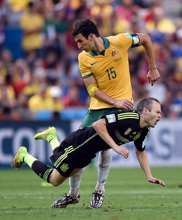 . Australia\'s Mile Jedinak fouls Spain\'s Andres Iniesta during the group B World Cup soccer match between Australia and Spain at the Arena da Baixada in Curitiba, Brazil, Monday, June 23, 2014. (AP Photo/Martin Meissner)