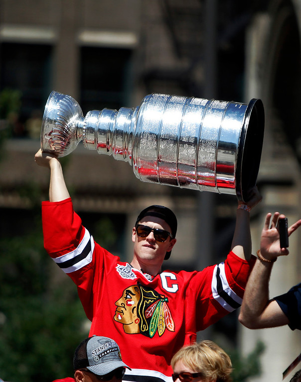 . Chicago Blackhawks\' Jonathan Toews holds up the 2013 Stanley Cup during a victory parade down Washington Street Friday, June 28, 2013 in Chicago. The Blackhawks celebrate the team\'s second championship in four years. (AP Photo/Scott Eisen)