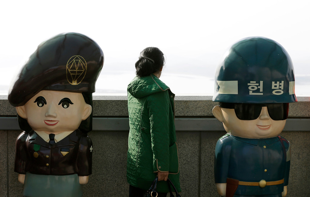 . A woman looks at North Korean territory next to dolls of South Korean soldiers at the unification observation post near the border village of Panmunjom, which has separated the two Koreas since the Korean War, in Paju, north of Seoul, South Korea, Monday, April 15, 2013. Foreign governments have been struggling to assess how seriously to take North Korea\'s recent torrent of rhetoric ó including warnings of possible nuclear war ó as it expresses its anger over continuing U.S.-South Korea military maneuvers just across the border. Officials in South Korea, the United States and Japan say intelligence indicates that North Korean officials, fresh off an underground nuclear test in February, are ready to launch a medium-range missile. (AP Photo/Lee Jin-man)