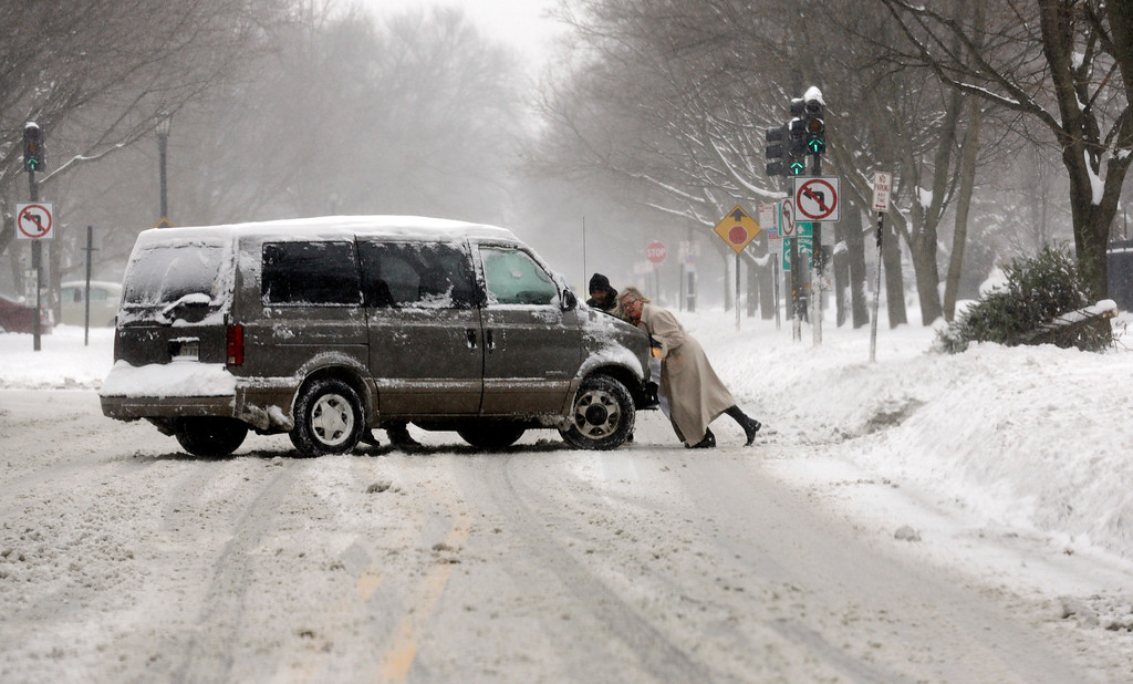 . People push a car on a snowy road in Chicago on Sunday, Jan. 5, 2014. Sunday night temperatures will drastically drop to about minus 20 degrees. (AP Photo/Nam Y. Huh)