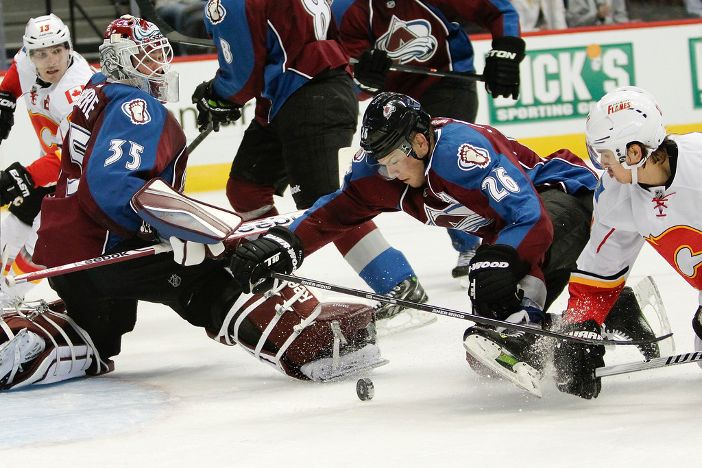 . Colorado Avalanches\' Paul Stastny (26) and Calgary Flames\' Mikael Backlund (11), of Sweden, battle for the puck that goalie Jean-Sebastien Giguere (35) left open during the second period of an NHL hockey game on Friday, Nov. 8, 2013, in Denver. (AP Photo/Barry Gutierrez)