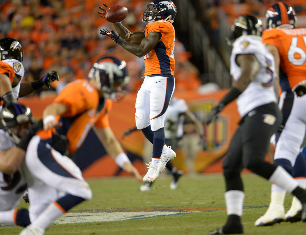 . DENVER, CO - SEPTEMBER 05: Denver Broncos running back Ronnie Hillman (21) makes a first down catch in the third quarter, why Denver Broncos quarterback Peyton Manning (18) gets taken down in the foreground.. Denver Broncos Baltimore Ravens September 5, 2013 at Sports Authority at Mile High. (Photo by Joe Amon/The Denver Post)