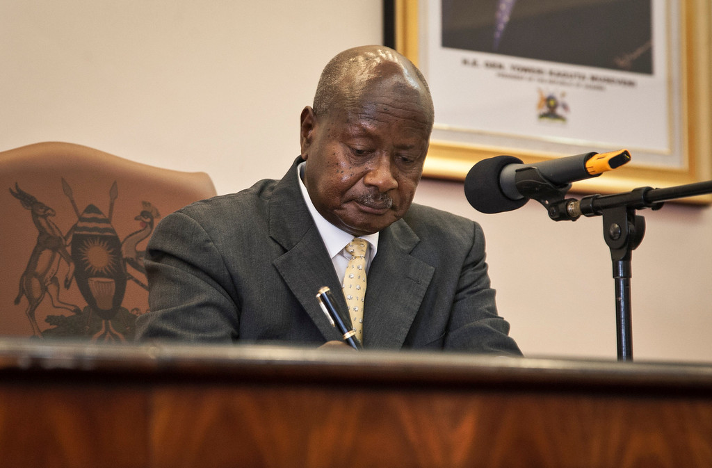 """. Uganda\'s President Yoweri Museveni signs a new anti-gay bill that sets harsh penalties for homosexual sex, in Entebbe, Uganda Monday, Feb. 24, 2014. Museveni on Monday signed the controversial anti-gay bill into law, with penalties including 14 years in jail for first-time offenders and life imprisonment as the maximum penalty for \""""aggravated homosexuality\"""", saying it is needed to deter what he called the West\'s \""""social imperialism\"""" promoting homosexuality in Africa. (AP Photo/Rebecca Vassie)"""