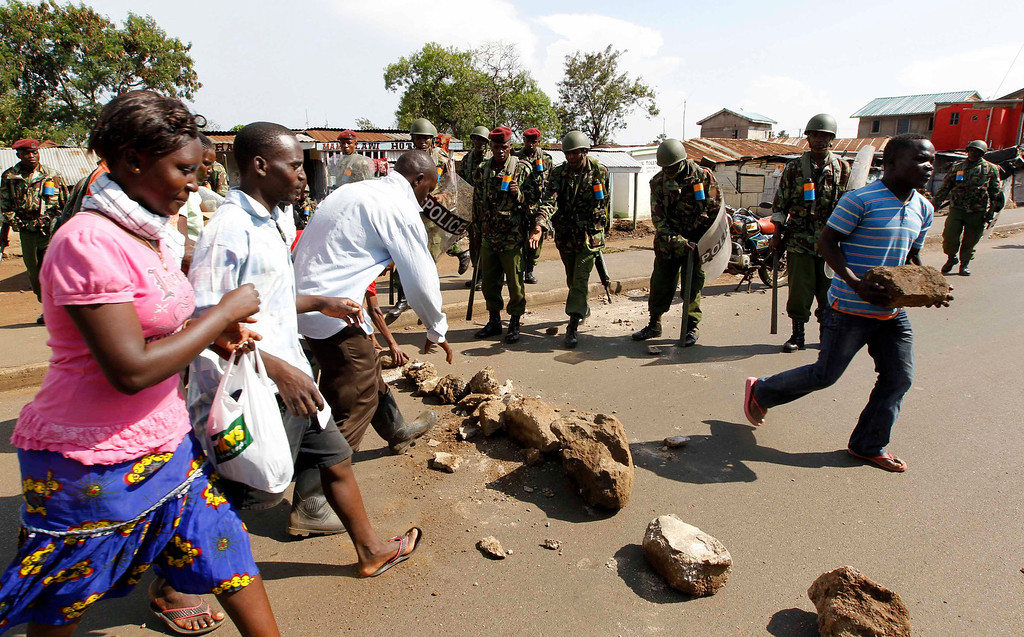 . Riot police and civilians remove a barricade along a road as tension arises after Uhuru Kenyatta was declared winner of Kenya\'s presidential election, in Nyallenda slums in Kenya\'s western town of Kisumu, 350km (218 miles) from the capital Nairobi, March 9, 2013. REUTERS/Thomas Mukoya