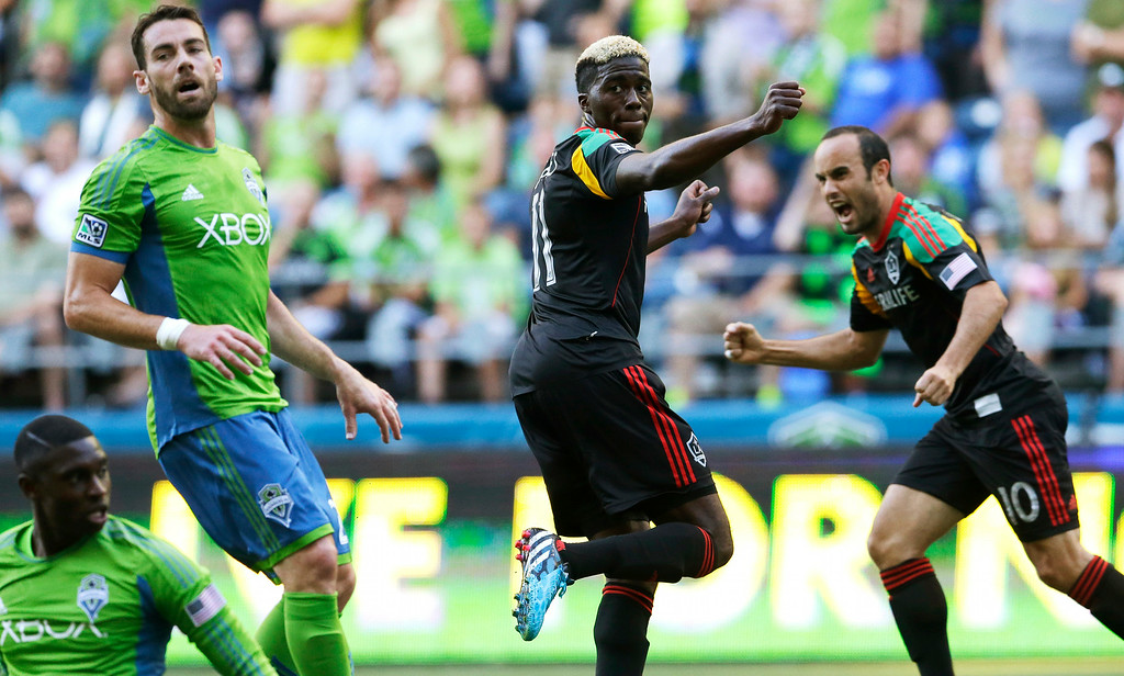 . Los Angeles Galaxy\'s Gyasi Zardes, center, and Landon Donovan, right, react next to Seattle Sounders\' Zach Scott, left, after Zardes scored a goal against the Sounders in the first half of an MLS soccer match, Monday, July 28, 2014, in Seattle. (AP Photo/Ted S. Warren)