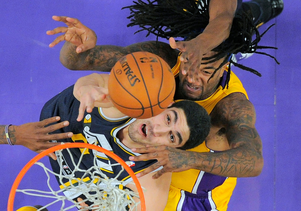. Utah Jazz center Enes Kanter, bottom, of Turkey, puts up a shot as Los Angeles Lakers center Jordan Hill defends during the first half of an NBA basketball game, Friday, Jan. 3, 2014, in Los Angeles. (AP Photo/Mark J. Terrill)