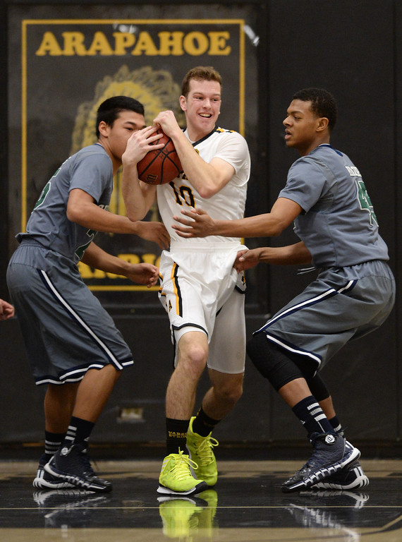 . CENTENNIAL, CO. JANUARY 18: Corbin Atwell of Arapahoe High School (10), center, controls the ball between Tyler Stevenson (25), left, and King Grant-Perry (45) of Overland High School during the 2nd half of the game at Arapahoe High School. Centennial Colorado. January 18. 2014. Arapahoe won 62-54.  (Photo by Hyoung Chang/The Denver Post)
