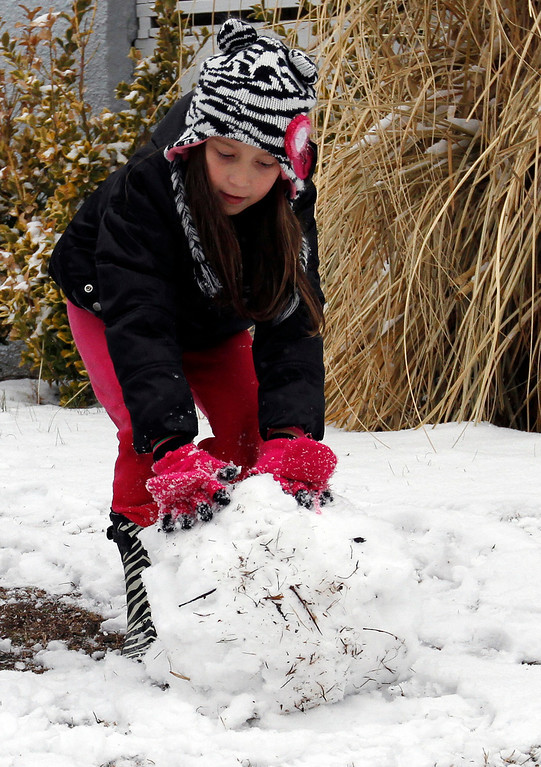 . Adrianne Lynn DeBruhl, of Cullman, rolls up a snow ball to put on her snowman on Tuesday, Feb. 11, 2014, in Cullman, Ala. A winter storm dropped several inches of snow on North Alabama overnight and more is expected. (AP Photo/Butch Dill)