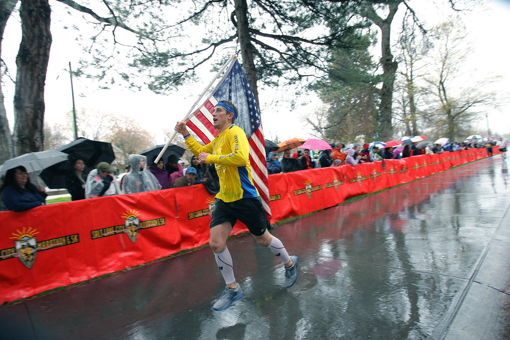 . A competitor runs with the American flag to the finish line of the Salt Lake City marathon, Saturday, April 20, 2013, Salt Lake City.  (AP Photo/Melissa Majchrzak)
