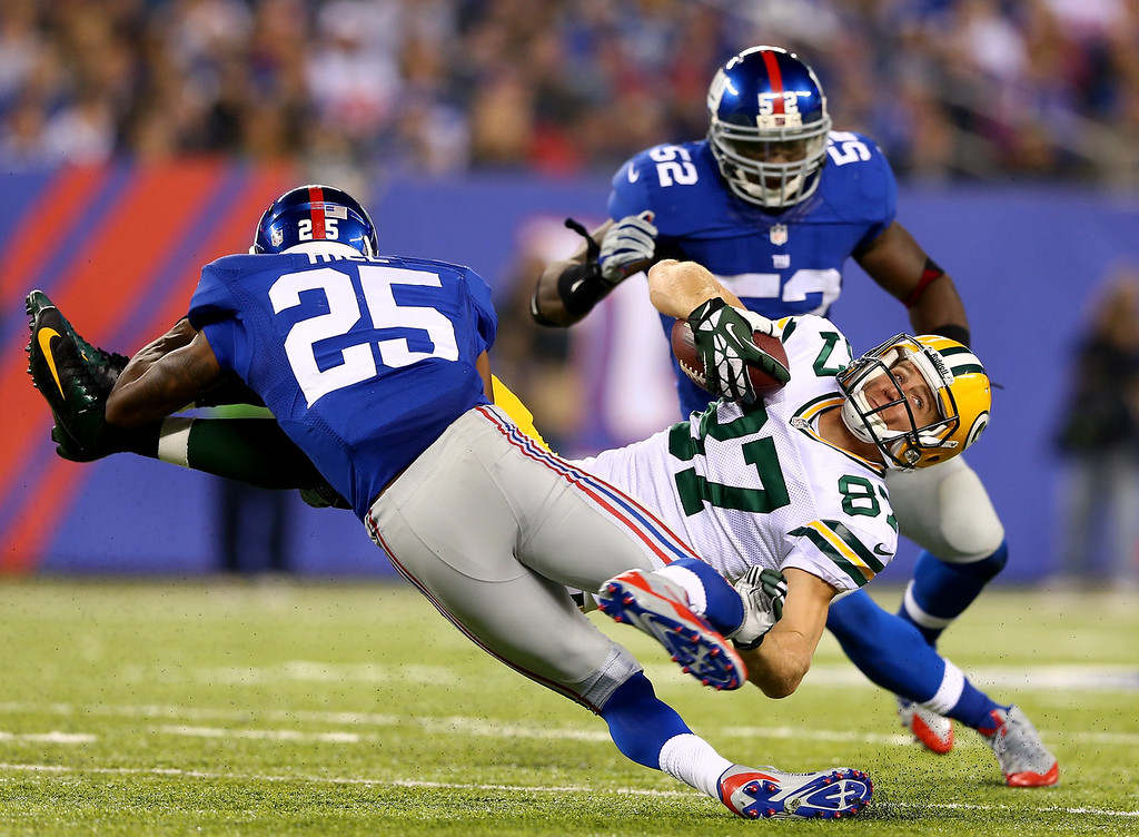 . Jordy Nelson #87 of the Green Bay Packers collides with Will Hill #25 of the New York Giants as  Jon Beason #52 of the Giants stands by in the second half at MetLife Stadium on November 17, 2013 in East Rutherford, New Jersey.The New York Giants defeated the Green Bay Packers 27-13.  (Photo by Elsa/Getty Images)