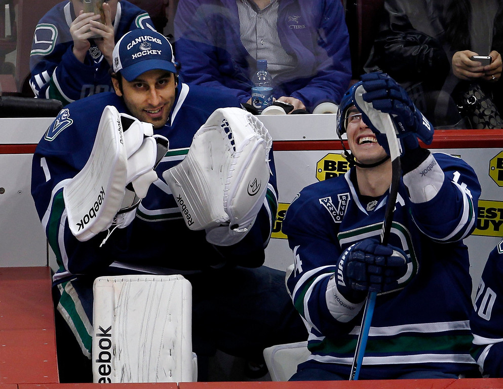 . Vancouver Canucks goalie Roberto Luongo (L) jokes with teammate Alex Burrows on the bench during the third period of their NHL hockey game against the Colorado Avalanche in Vancouver, British Columbia March 28, 2013.   REUTERS/Andy Clark