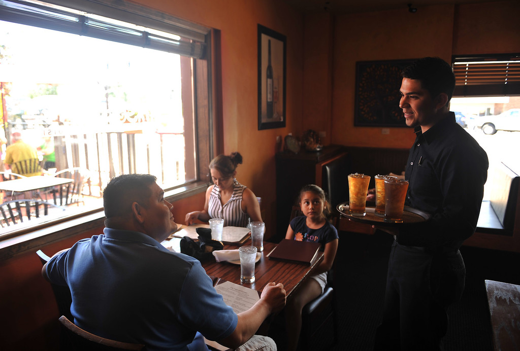 . Manager Mike Perez, right, explains about menu to the customers at Tapas D\' Jerez, traditional spanish restaurant. Centennial, Colorado. July 18, 2013. (Photo By Hyoung Chang/The Denver Post)
