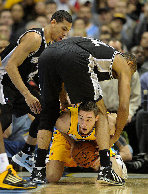. Denver forward Danilo Gallinari (8) tried to sneak the ball through the legs of Spurs forward Tim Duncan (21) in the first half. The Denver Nuggets hosted the San Antonio Spurs at the Pepsi Center Tuesday night, December 18, 2012. Karl Gehring/The Denver Post