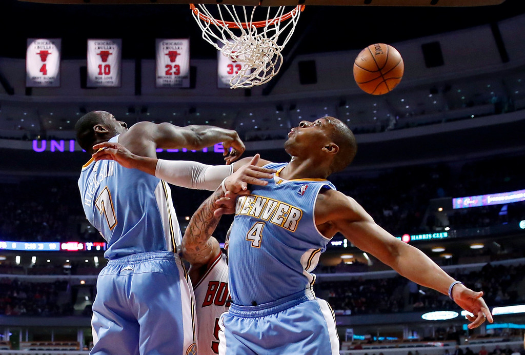 . Denver Nuggets center J.J. Hickson (7) blocks the shot of Chicago Bulls forward Carlos Boozer as Randy Foye (4) also defends during the first half of an NBA basketball game Friday, Feb. 21, 2014, in Chicago. (AP Photo/Charles Rex Arbogast)