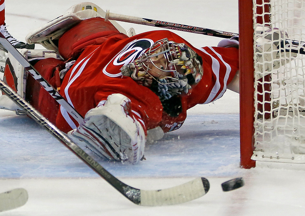 . Carolina Hurricanes goalie Justin Peters (35) eyes the puck as a teammate clears during the first period of an NHL hockey game against the Colorado Avalanche in Raleigh, N.C., Tuesday, Nov. 12, 2013. (AP Photo/Karl B DeBlaker)