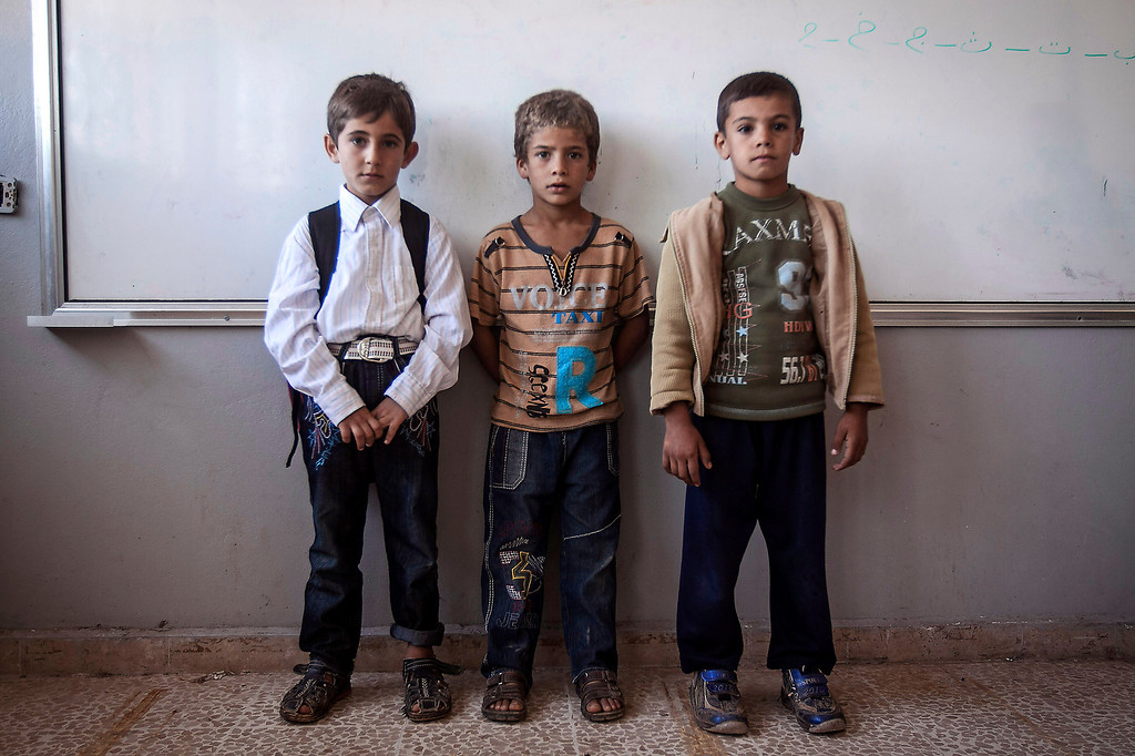 . In this Thursday, Sept. 26, 2013 photo, Syrian children pose for a portrait in their classroom in the public school in Madaya village as classes begin in the Idlib province countryside of Syria. Millions of Syrian children most of them in government-controlled areas have returned to school in the past two weeks, despite the conflict that according to UNICEF has left 4,000 Syrian schools or one in five damaged, destroyed or sheltering displaced families. (AP Photo)