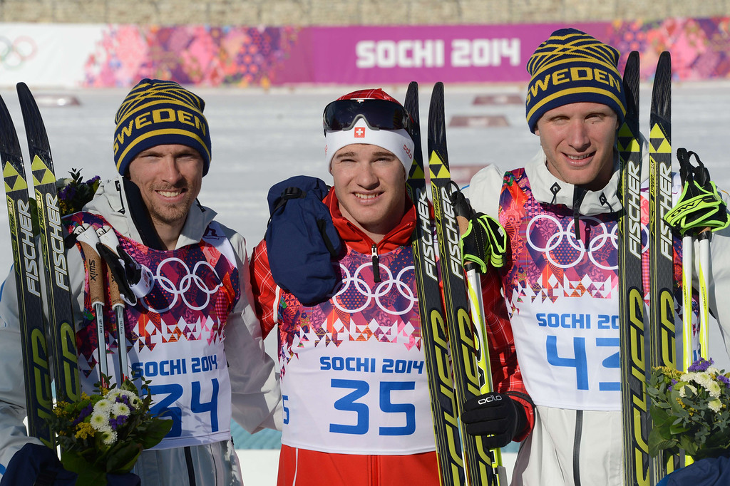 . From left to right:- Silver medalist Sweden\'s Johan Olsson, gold medalist Switzerland\'s Dario Cologna and bronze medalist Sweden\'s Daniel Richardsson celebrate on the podium in the Men\'s Cross-Country Skiing 15km Classic Flower Ceremony at the Laura Cross-Country Ski and Biathlon Center during the Sochi Winter Olympics on February 14, 2014 in Rosa Khutor near Sochi. AFP PHOTO / KIRILL KUDRYAVTSEV/AFP/Getty Images