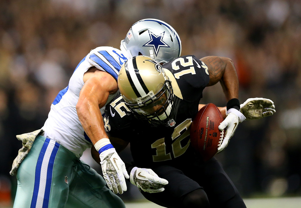 . Wide receiver Marques Colston #12 of the New Orleans Saints  avoids a tackle by strong safety Jeff Heath #38 of the Dallas Cowboys in the first quarter during a game at the Mercedes-Benz Superdome on November 10, 2013 in New Orleans, Louisiana.  (Photo by Ronald Martinez/Getty Images)