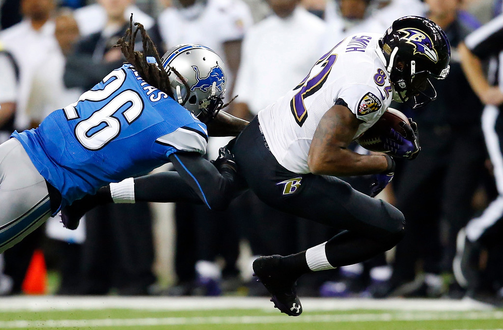 . Baltimore Ravens wide receiver Torrey Smith (82) is stopped by Detroit Lions free safety Louis Delmas (26) during the second quarter of an NFL football game in Detroit, Monday, Dec. 16, 2013. (AP Photo/Rick Osentoski)