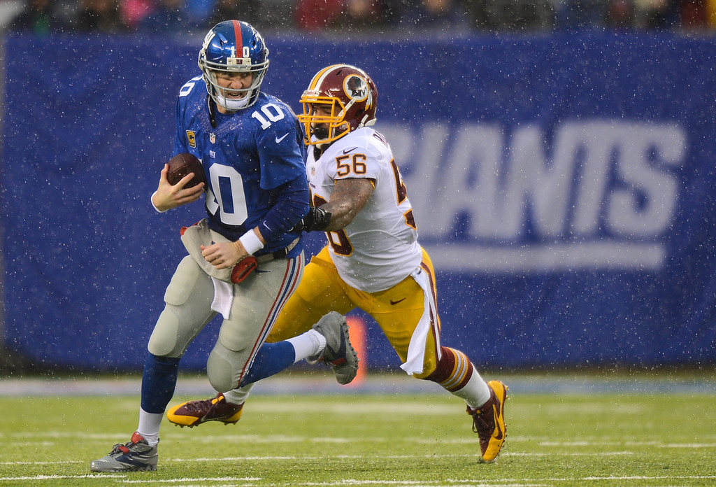 . Quarterback Eli Manning #10 of the New York Giants is sacked by inside linebacker Perry Riley #56 of the Washington Redskins in the first half  at MetLife Stadium on December 29, 2013 in East Rutherford, New Jersey. (Photo by Ron Antonelli/Getty Images)