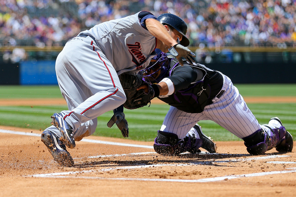 . Catcher Wilin Rosario #20 of the Colorado Rockies tags out Brian Dozier #2 of the Minnesota Twins for the second out of the first inning at Coors Field on July 13, 2014 in Denver, Colorado. (Photo by Justin Edmonds/Getty Images)