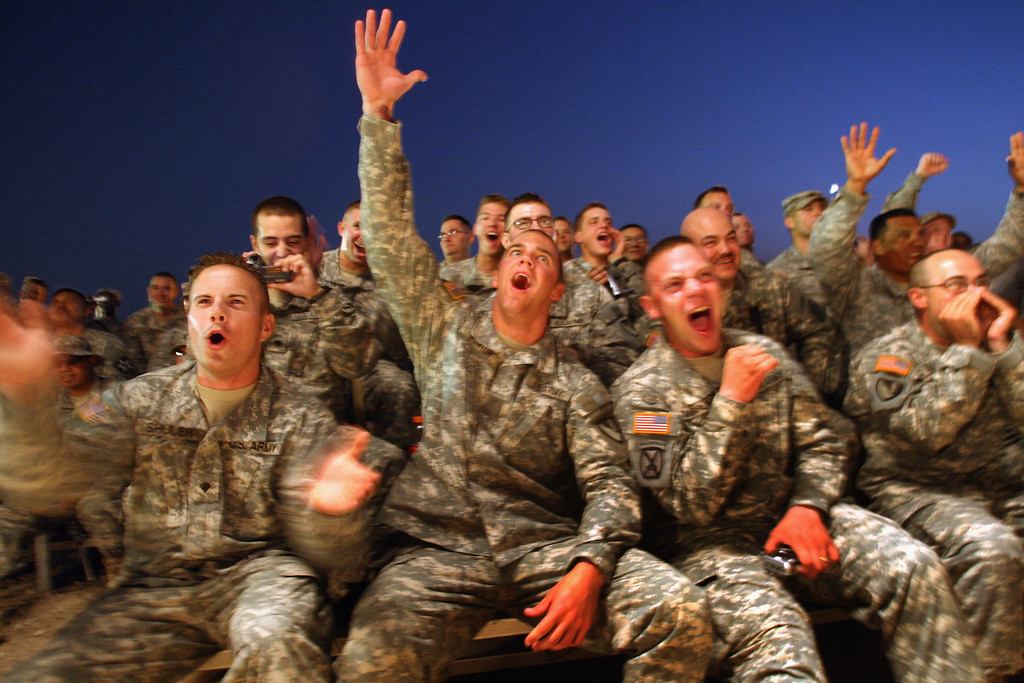. American soldiers cheer as the Dallas Cowboys Cheerleaders take the stage as part of a military USO tour of Iraq September 15, 2007 in Baghdad, Iraq. The cheerleaders, on their first trip to Iraq, were doing 5 shows throughout the country for the soldiers, many of whom were on 15 month deployments.  (Photo by John Moore/Getty Images)