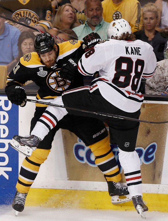 . Chicago Blackhawks\' Patrick Kane (R) checks Boston Bruins\' Andrew Ference during the second period in Game 6 of their NHL Stanley Cup Finals hockey series in Boston, Massachusetts, June 24, 2013. REUTERS/Winslow Townson