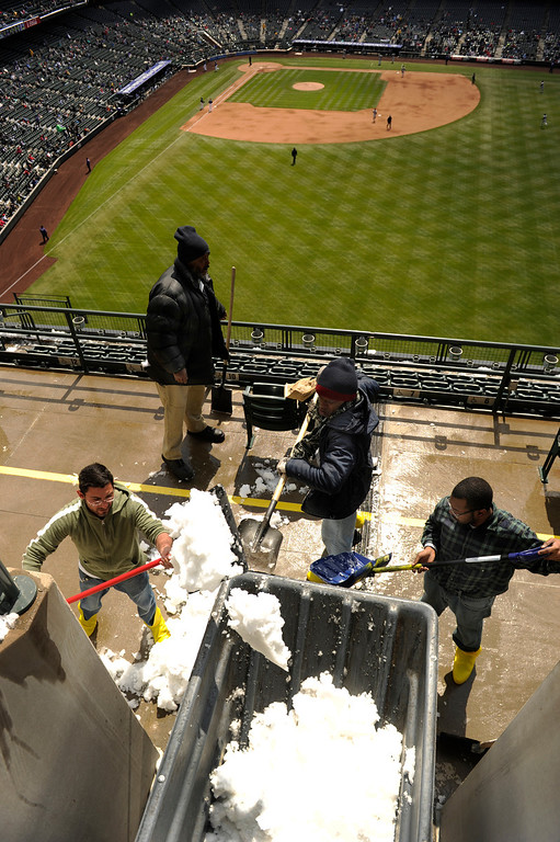 . DENVER, CO. - APRIL 23:  Day laborers cleared the upper deck seats of snow during the first game of a doubleheader Tuesday. From left, Rocky Gallegos, Thomas Greenwood, Frederick Greer, and Demetrius Chapman, loaded snow into a container. The Atlanta Braves defeated the Colorado Rockies 4-3 at Coors Field Tuesday, April 23, 2013.  The first game of the doubleheader Tuesday was a make-up from Monday night\'s postponement due to weather.  Photo By Karl Gehring/The Denver Post