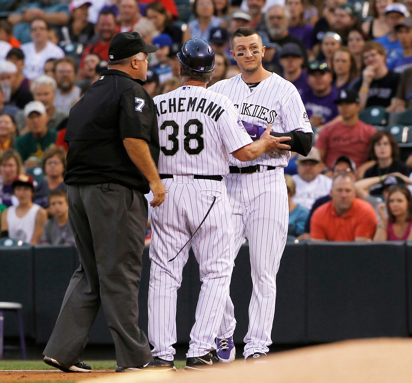. Colorado Rockies\' Troy Tulowitzki, right, is blocked by first base coach Rene Lachemann, center, as Tulowitzki argues that he beat out an infield grounder with first base umpire Brian O\'Nora against the Cincinnati Reds in the first inning of a baseball game in Denver on Saturday, Aug. 31, 2013. (AP Photo/David Zalubowski)