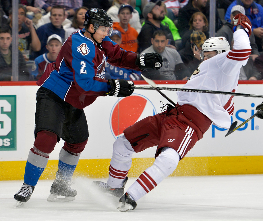 . Colorado Avalanche defenseman Nick Holden (2) knocks Phoenix Coyotes center Martin Hanzal (11) off his skates during the second period of an NHL hockey game on Friday, Feb. 28, 2014, in Denver. (AP Photo/Jack Dempsey)