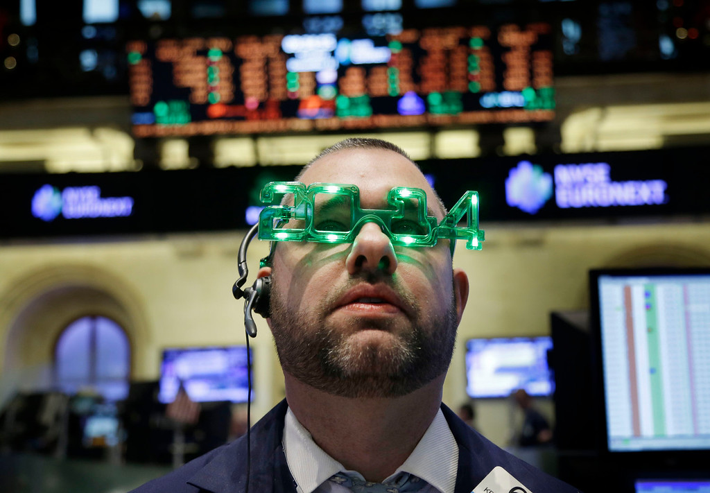 . A trader wears glasses celebrating the new year while working on the floor at the New York Stock Exchange in New York, Tuesday, Dec. 31, 2013.  (AP Photo/Seth Wenig)
