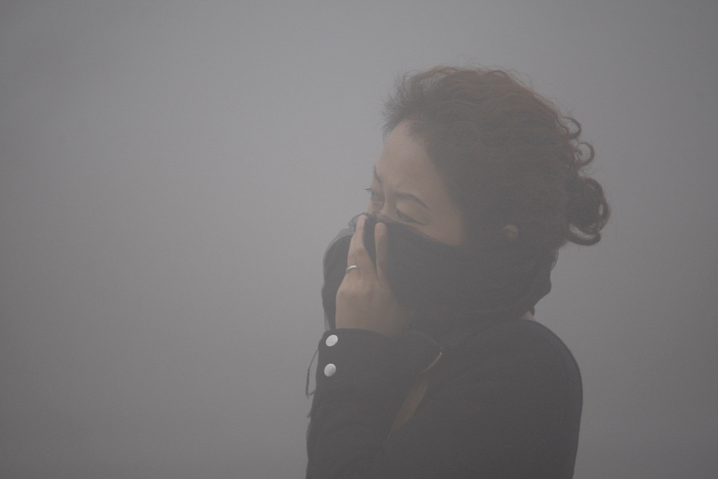 . A  woman covers her mouth with her scarf in the smog in Harbin, northeast China\'s Heilongjiang province, on October 21, 2013.     AFP PHOTOSTR/AFP/Getty Images