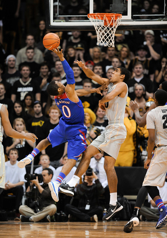 . Colorado University forward, Josh Scott, right, defends a shot attempt by Kansas guard, Frank Mason, in the second half of play at the Coors Events Center in Boulder Colorado Saturday afternoon, December 07, 2013. (Photo By Andy Cross/The Denver Post)