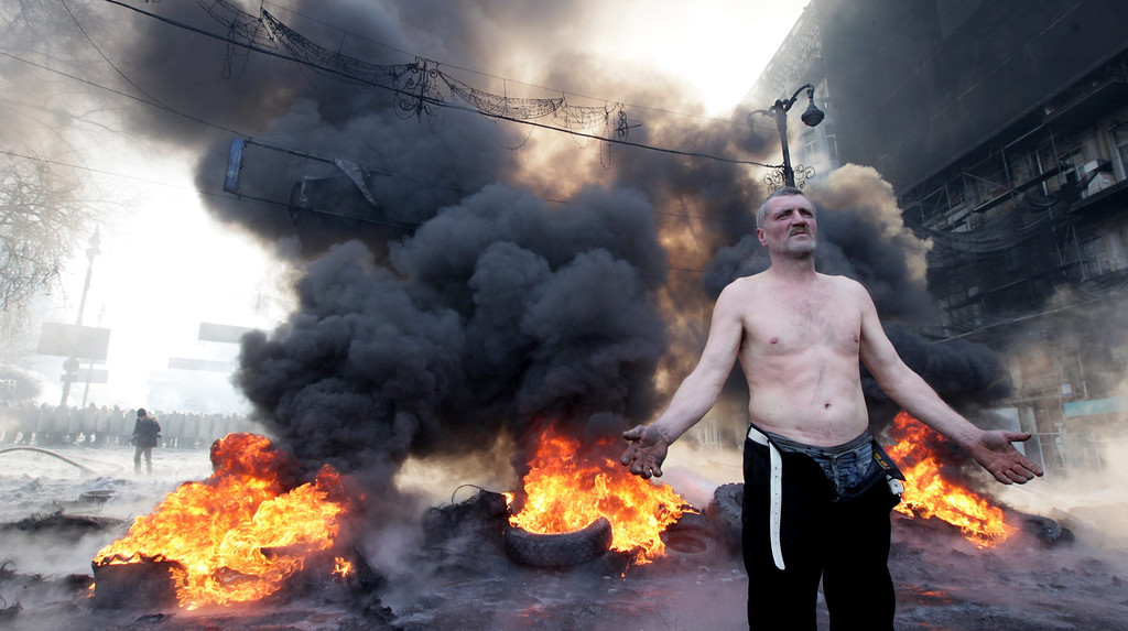 . A man stands next to the burning tires during an anti-government protest in downtown Kiev, Ukraine, 25 January 2014. Ukraine has been convulsed by protests led by pro-European activists incensed that President Viktor Yanukovych opted against an association agreement with the European Union in November, choosing closer relations with Russia instead. According to media reports on 25 January, more fighting was reported overnight in Kiev, with demonstrators throwing rocks and flaming objects at security forces.  EPA/ZURAB KURTSIKIDZE