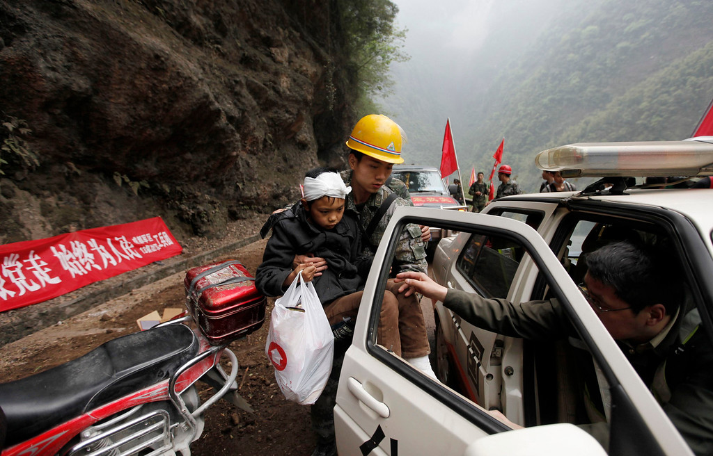 . A rescuer carries an injured survivor into a car near a landslide caused by Saturday\'s earthquake, on a road to Lingguan township, in Baoxing county in Ya\'an, Sichuan province April 22, 2013. REUTERS/Jason Lee