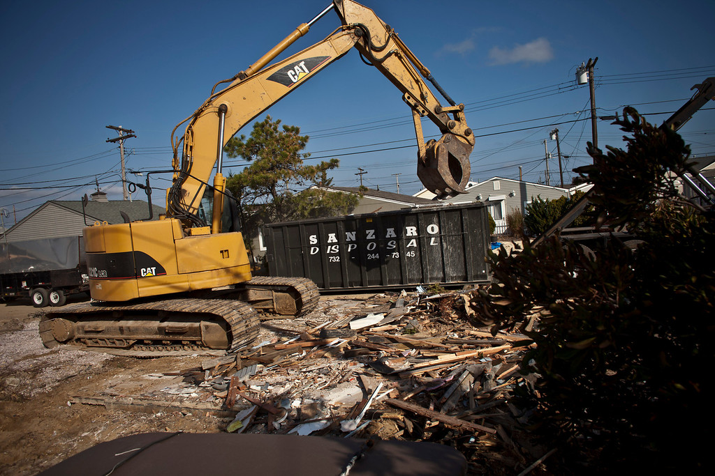 . A machine works on a demolition of a house one year after being partially destroyed by Superstorm Sandy, October 29, 2013 in Dover Beach North, New Jersey. (Photo by Kena Betancur/Getty Images)