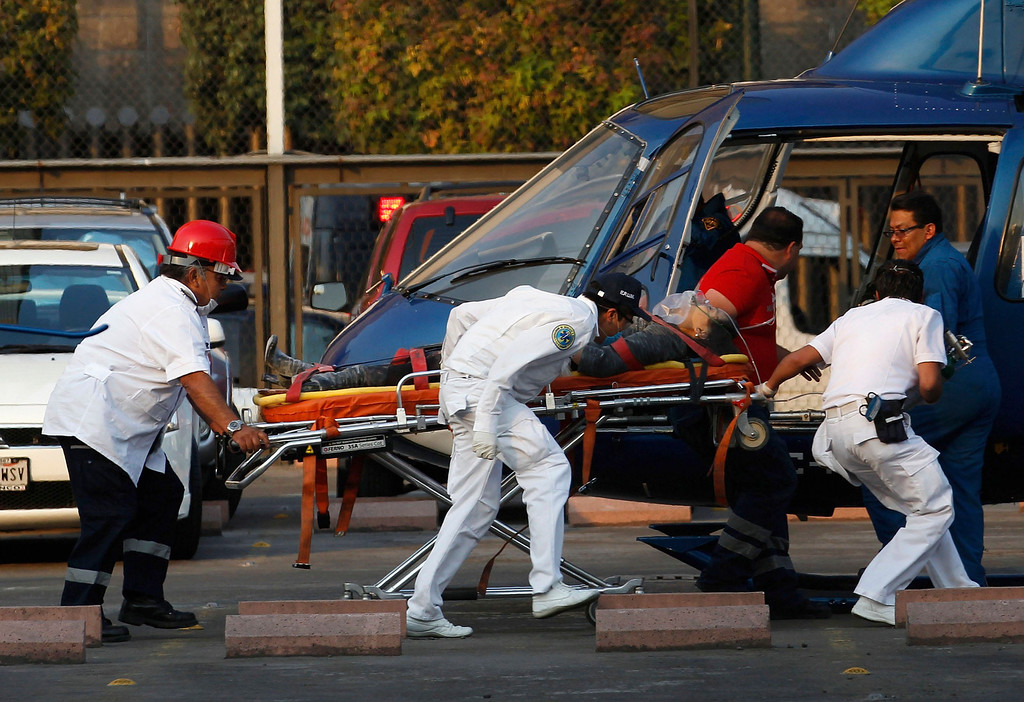 . Paramedics wheel an injured person to a helicopter at the parking lot of the state-run oil company Pemex after an explosion in Mexico City January 31, 2013. An explosion rocked the Mexico City headquarters of state oil giant Pemex on Thursday, killing at least 14 people and injuring 80 people, Interior Minister Miguel Angel Osorio Chong said on Thursday. The death toll could still rise, he told local television. The blast, which media reports said was caused by machinery exploding, occurred in the basement, emergency officials said. REUTERS/Tomas Bravo