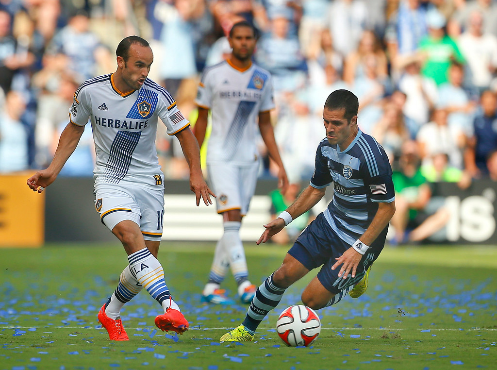. The LA Galaxy\'s Landon Donovan passes the ball ahead of Sporting Kansas City\'s Benny Feilhaber during the first half of a soccer match,  Saturday, July 19, 2014, at Sporting Park in Kansas City, Kan. (AP Photo/The Topeka Capital Journal, Chris Neal)