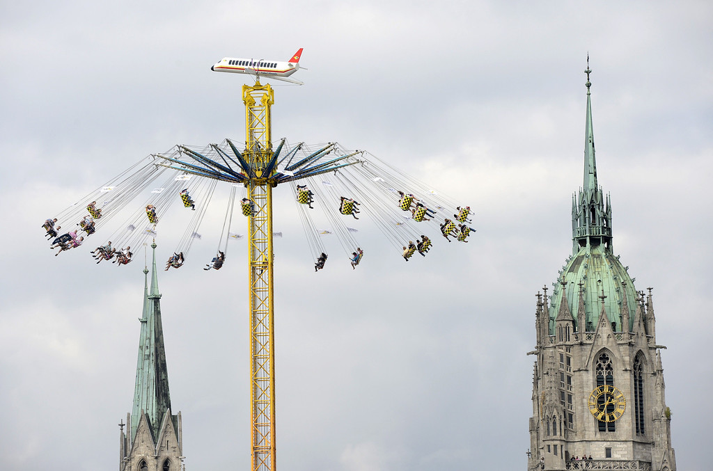 . Visitors sits in a fairground ride in front of the St. Pauls church at the Oktoberfest beer festival at the Theresienwiese in Munich, southern Germany, on September 21, 2013. The world\'s biggest beer festival Oktoberfest will run until October 6, 2013.  AFP PHOTO / CHRISTOF  STACHE/AFP/Getty Images