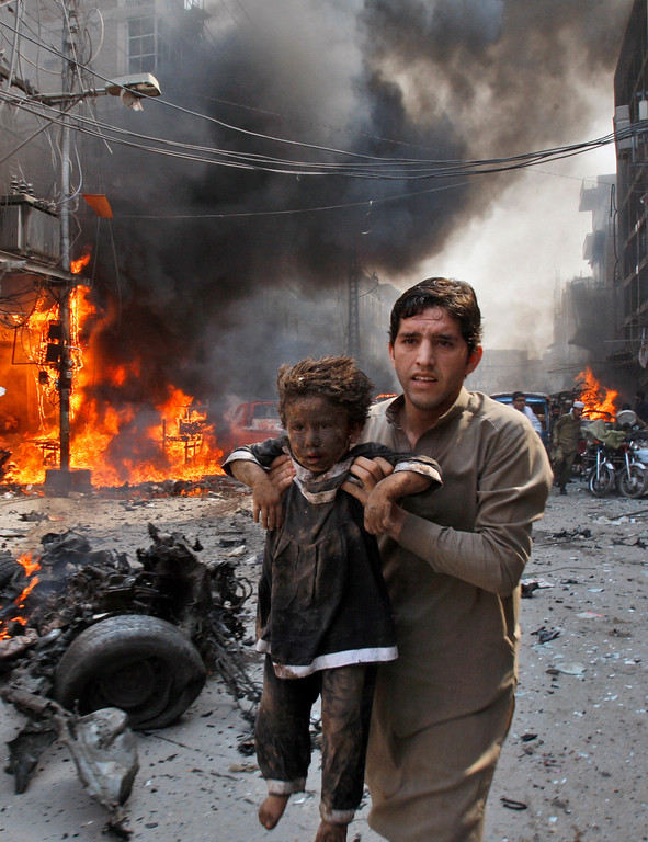 . A Pakistani man carrying a child rushes away from the site of a blast shortly after a car bomb exploded in Peshawar, Pakistan, Sunday, Sept. 29, 2013.  (AP Photo/Mohammad Sajjad)
