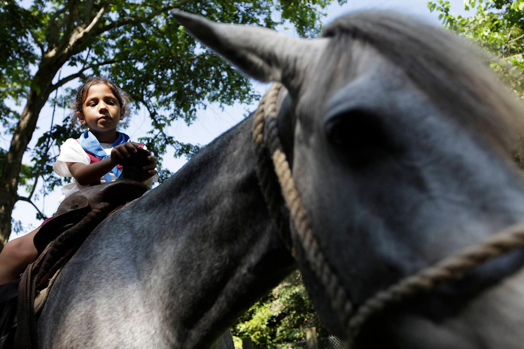 . An autistic girl who is a student at the Dora Alonso School rides a horse during a equine-assisted therapy session at the Cuban National Zoo in Havana on June 13, 2013. Students of the Dora Alonso School, which specializes in treating children who suffer from autism spectrum disorders, periodically visit the zoo to learn to interact with different animals as part of their therapy.  REUTERS/Enrique De La Osa